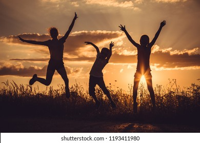 Silhouette of three happy children which playing on the field at the sunset time. People having fun outdoors. Concept of friendly family.