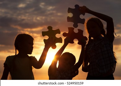 Silhouette of three happy children which playing on the field at the sunset time. They having fun on the nature. Concept of the kids are ready to go to school.