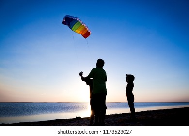 Silhouette of three kids on the lake coas launching the rainbow kite together at sunset