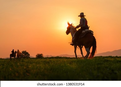 The silhouette of three men wearing a cowboy dress with horses and guns held in the hand