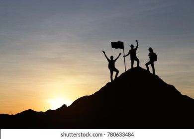 Silhouette of three people are celebrating success at the top of the mountain, sky and sun light background. Business, successful, leadership, achievement, teamwork and goal concept.