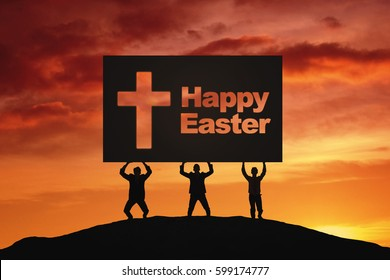 Silhouette of three people lifting big board with text of Happy Easter and crucifix symbol while standing on the hill