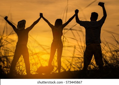 The silhouette of three people show joined hands with sunset background. friendship concept.
