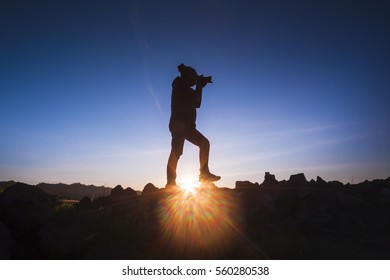 Silhouette of three photographers on a workshop at sunrise taking landscape images with cameras, backpacks and tripods