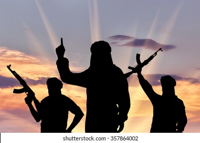 Silhouette of three terrorists with weapons dictate their terms at sunset