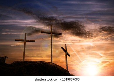 Silhouette of three wooden crosses above the hill with dramatic sky and sun rays at sunset. Religious symbol of good friday
