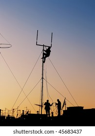 silhouette of three workers repairing communication antenna on the roof top full of TV and satellite antenna at sunset