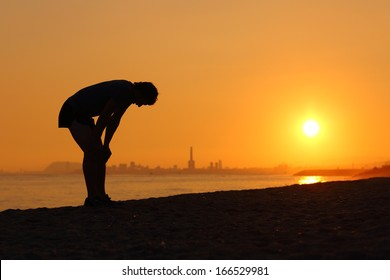 Silhouette of an tired sportsman at sunset with a city in the background