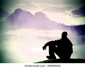 Silhouette of tired tourist in windcheater and dark cap sit on rock and watching into blue misty valley bellow. Sunny spring daybreak in rocky mountains.