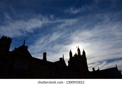 Silhouette of top of The Quadrangle building in University Of Sydney. Sydney Uni building facade with Australian flag. University of Sydney against deep blue sky with white clouds.