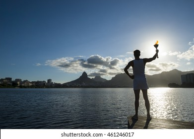 Silhouette of torchbearer athlete standing with sport torch against the setting sun of the Rio de Janeiro Brazil skyline at Lagoa Rodrigo de Freitas lagoon
