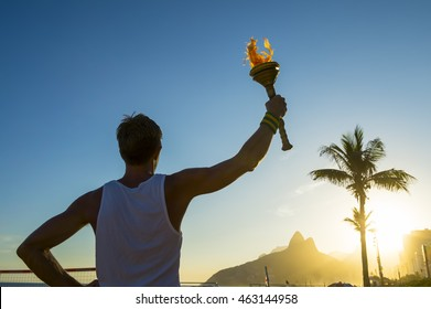 Silhouette of torchbearer athlete standing with sport torch in front of the Rio de Janeiro, Brazil sunset skyline at Ipanema Beach