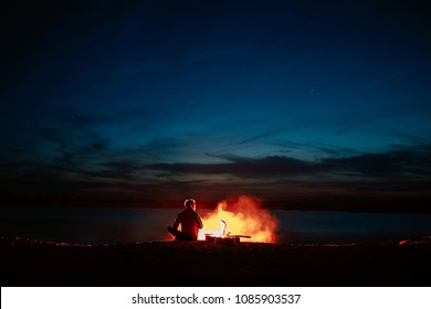 Silhouette of tourist around campfire at night on the river shore