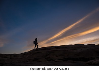 Silhouette tourist  girl who climb over the rock mountains with twilight sunset golden moment as background.