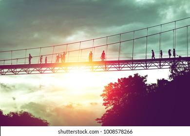 silhouette of tourist on suspension bridge walkway to the jungle in Surat Thani provine Thailand.