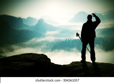 Silhouette of tourist with poles in hand. Hiker stand on rocky view point above misty valley. Sunny spring daybreak in rocky mountains