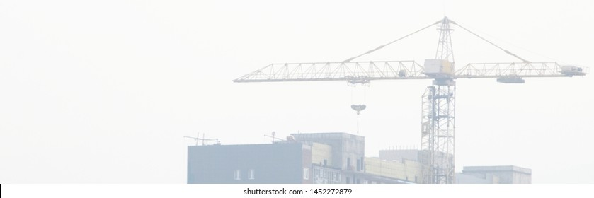 Silhouette of a tower crane and an unfinished house in a strong fog, wide format, a great white background for a signature or logo.
