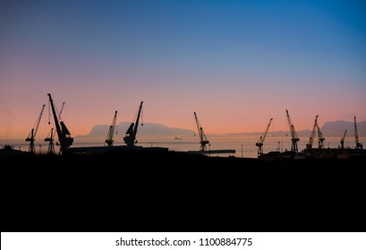 Silhouette of tower cranes in the commercial seaport of Palermo, Italy at sunset.