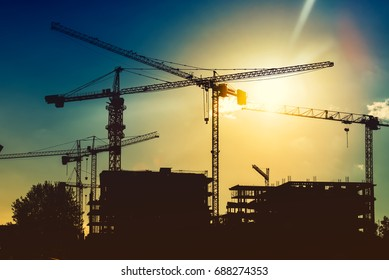 Silhouette of tower cranes on industrial construction site. New district development and skyscraper building