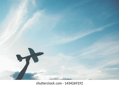 Silhouette of a toy plane in the hand against the sky