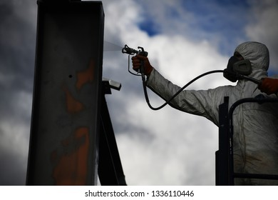 Silhouette of a tradesman spray painting the steel beams on a construction site