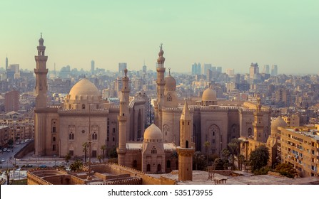 Silhouette of traditional arabic city with minarets. Mosque of Al Rifai and Madrasa of Sultan Hassan - panoramic view of old town in Cairo. Cityscape with landmarks of muslim architecture.