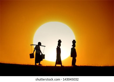 silhouette of traditional asian farmer coming back from a harvest with beautiful sunset