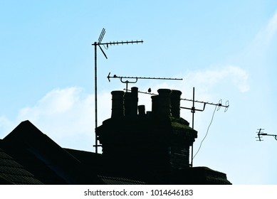 Silhouette of traditional British roof with chimneys and aerials