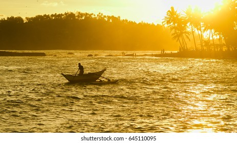 Silhouette of traditional fishermen on wooden boat at the sunset near Mirissa in Sri Lanka