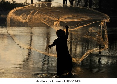 Silhouette of traditional fishermen throwing net fishing