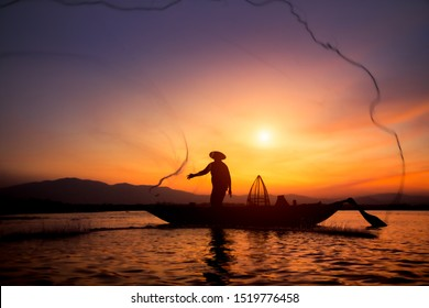 Silhouette of traditional fishermen throwing net fishing lake at sunrise time,thailand (The casting people living along the River)