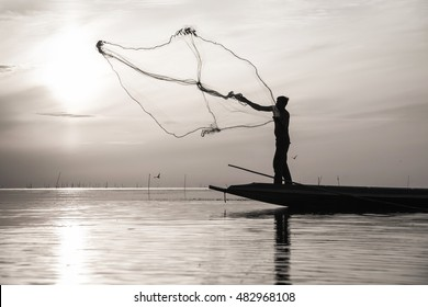 Silhouette of traditional fishermen throwing net fishing at sunrise time, livelihoods of fishermen at Pakpra, Phattalung in Thailand
