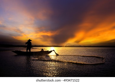 Silhouette of traditional fishermen throwing net fishing lake at sunrise time.(The casting people living along the River)