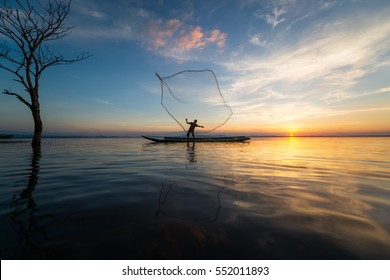 Silhouette of traditional fishermen throwing net fishing lake at sunset time,Asia,Thailand