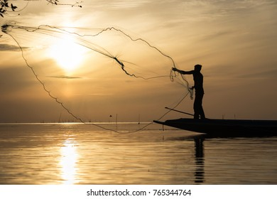Silhouette of traditional fishermen throwing net fishing at sunrise time, livelihoods of fishermen at Pakpra, Phatthalung in Thailand
