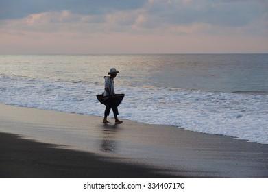 Silhouette of traditional salt farmer at Kusamba Bali Island, Indonesia