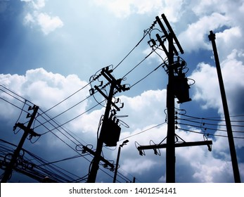 Silhouette of transformers and electrical wires on the pole On a blue sky background and sunny white clouds.