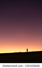 Silhouette travel people standing on mountain with sunset sky gradient color background.Lonely people on earth.