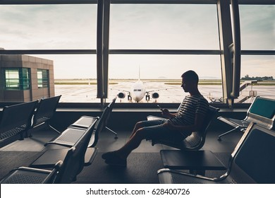 Silhouette of the traveler inside airport terminal. Young man using mobile phone and waiting for his flight.