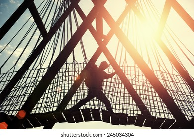 silhouette of a traveler man walking over hanging bridge in bright sunset