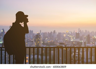 silhouette traveler photographer take a photo at rooftop of skyscrapers in sunset evening time.