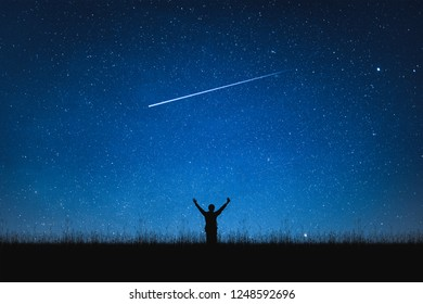 Silhouette of traveler standing on mountain and night sky with stars. Space background.