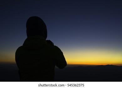 Silhouette Traveler taking photograph.