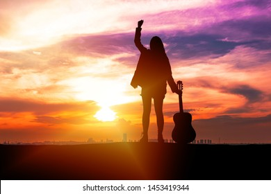 Silhouette traveler young women musician holding guitar and her hand while standing on sunset background with copy space. Beautiful sky sunrise with young girl feeling freedom with acoustic guitar.