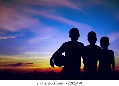 silhouette of tree kids standing after  play football with landscape of blue sky sunset background