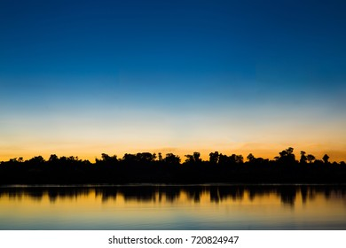 Silhouette of tree and river with beautiful color on sunset