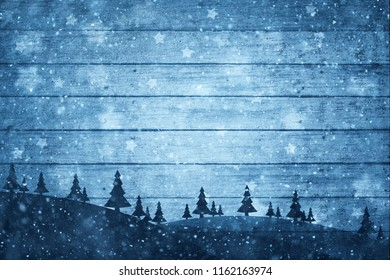 Silhouette of trees on the hills with textured wooden planks st snowy day. Blue Christmas and New Year holiday greeting card background.