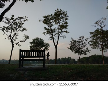 Silhouette from trees, park bench, and people exercising in Bedok Reservoir, Singapore.