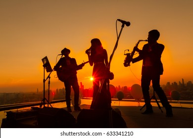 Silhouette trio musician, trio band showing on sunset light background, Bangkok Thailand