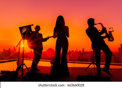 Silhouette trio musician, Trio band showing on sunset light background, Three musicians working on sky terrace, Bangkok Thailand